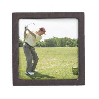 Senior golfer hitting practice balls at a range gift box