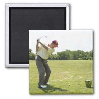Senior golfer hitting practice balls at a range magnet