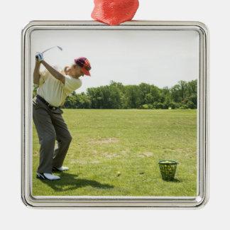Senior golfer hitting practice balls at a range metal ornament