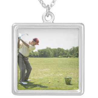 Senior golfer hitting practice balls at a range silver plated necklace