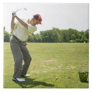 Senior golfer hitting practice balls at a range tile