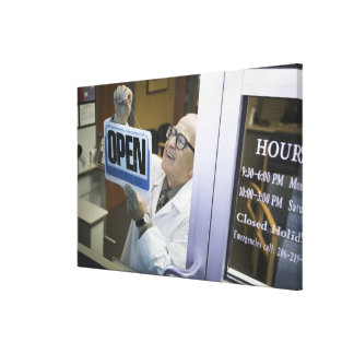Senior male pharmacist hanging 'Open' sign in Canvas Print