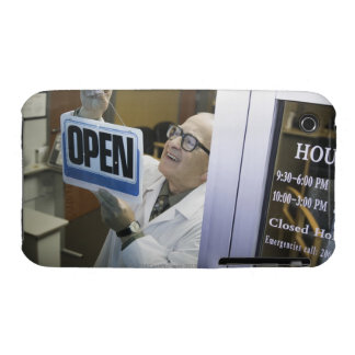Senior male pharmacist hanging 'Open' sign in iPhone 3 Case