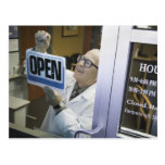 Senior male pharmacist hanging 'Open' sign in Postcard
