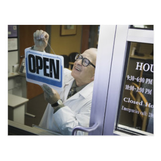 Senior male pharmacist hanging 'Open' sign in Postcard