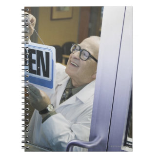 Senior male pharmacist hanging 'Open' sign in Spiral Notebook