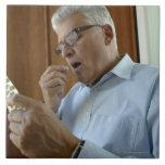 Senior man taking pill tile