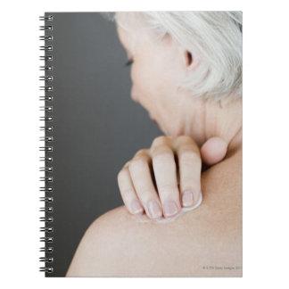 Senior woman applying moisturising cream to her notebook