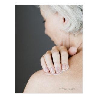 Senior woman applying moisturising cream to her postcard