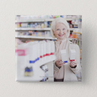 Senior woman comparing packages in drug store button