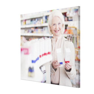 Senior woman comparing packages in drug store canvas print
