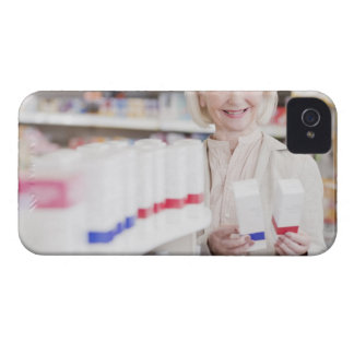 Senior woman comparing packages in drug store iPhone 4 cover