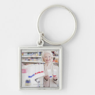 Senior woman comparing packages in drug store keychain