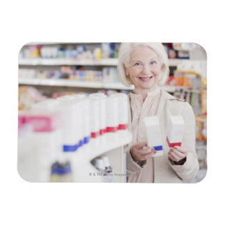 Senior woman comparing packages in drug store magnet