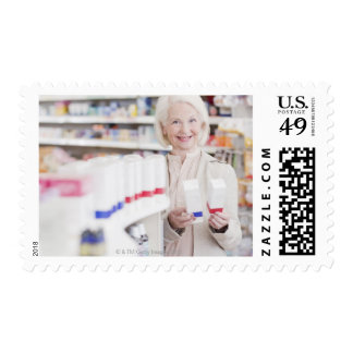 Senior woman comparing packages in drug store postage stamp