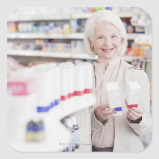 Senior woman comparing packages in drug store square sticker
