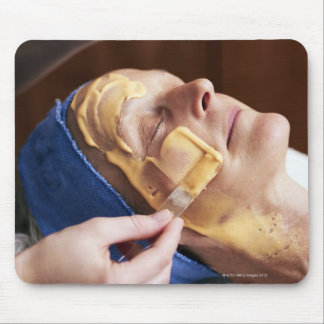 Senior woman having facial cream applied mouse pad