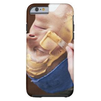 Senior woman having facial cream applied tough iPhone 6 case