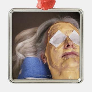 Senior woman having spa treament metal ornament