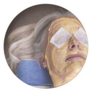 Senior woman having spa treament party plates