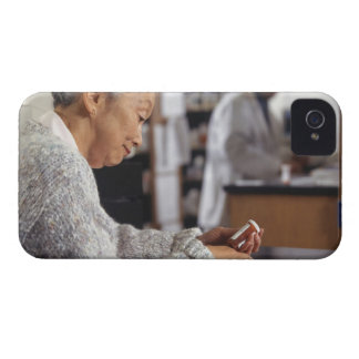 Senior woman in pharmacy reading medicine bottle Case-Mate iPhone 4 case
