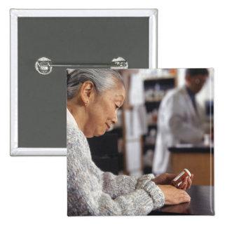 Senior woman in pharmacy reading medicine bottle pinback button