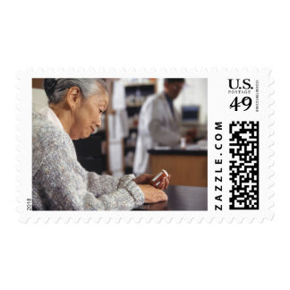 Senior woman in pharmacy reading medicine bottle postage