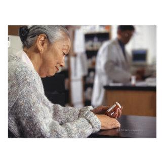 Senior woman in pharmacy reading medicine bottle postcard