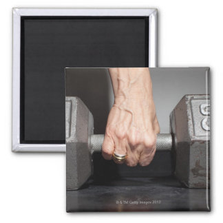 Senior woman lifting weights magnet