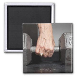 Senior woman lifting weights magnet