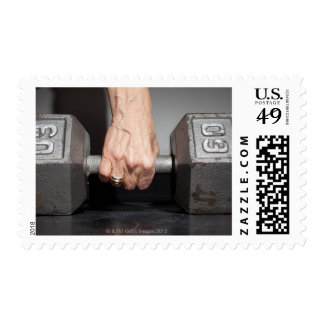 Senior woman lifting weights postage