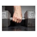 Senior woman lifting weights postcard