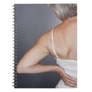 Senior woman with backache 2 spiral notebook