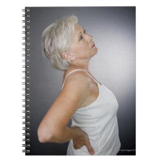 Senior woman with backache spiral notebook