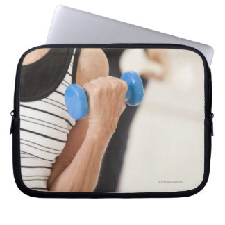 Seniors exercising with dumbbells in a health laptop computer sleeve