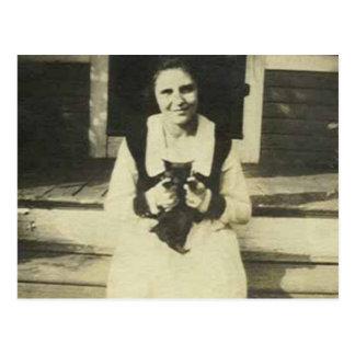señora que se sienta con la postal del gato negro