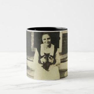 Señora que se sienta con la taza del gato negro