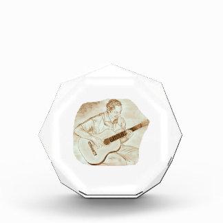 sepia que se sienta del jugador de la guitarra acú