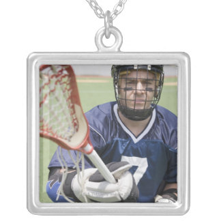 Serious lacrosse player holding crosse necklaces