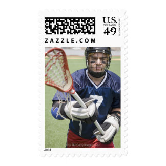 Serious lacrosse player holding crosse postage stamp
