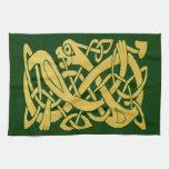 Serpiente céltica del oro en la toalla verde oscur
