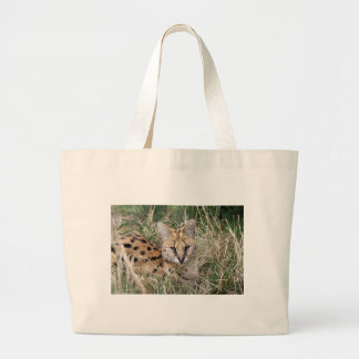 Serval cat relaxing in grass large tote bag