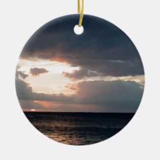 Setting sun over the ocean ceramic ornament