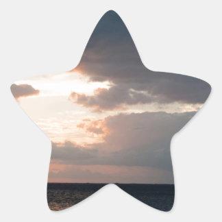 Setting sun over the ocean star sticker