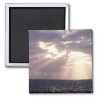 Setting sun shining through clouds over ocean fridge magnets