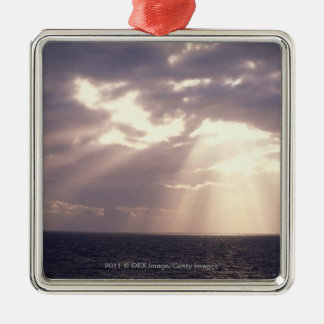 Setting sun shining through clouds over ocean square metal christmas ornament