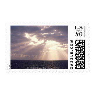 Setting sun shining through clouds over ocean postage