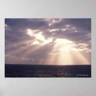Setting sun shining through clouds over ocean poster