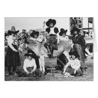 Seven rodeo cowgirls jokingly posing with a donkey card