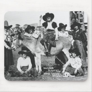 Seven rodeo cowgirls jokingly posing with a donkey mouse pad